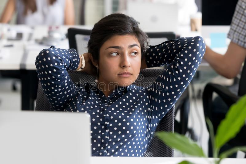 Thoughtful Indian female employee leaning back in chair at workp. Thoughtful peaceful Indian female employee looking in distance, leaning back in chair at royalty free stock photos