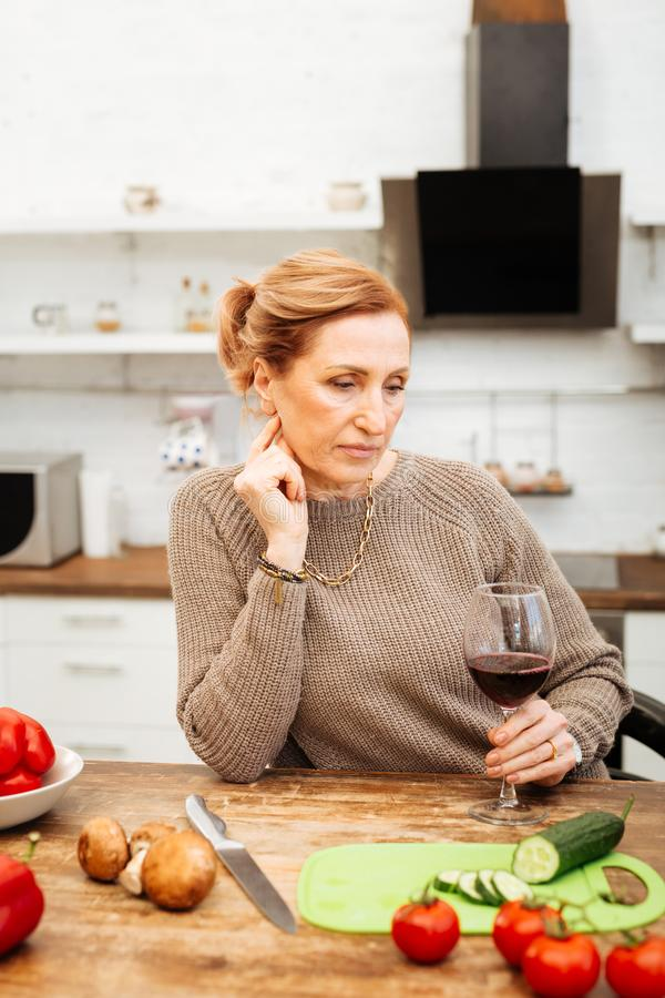 Thoughtful light-haired woman preparing light dinner with vegetables royalty free stock photos