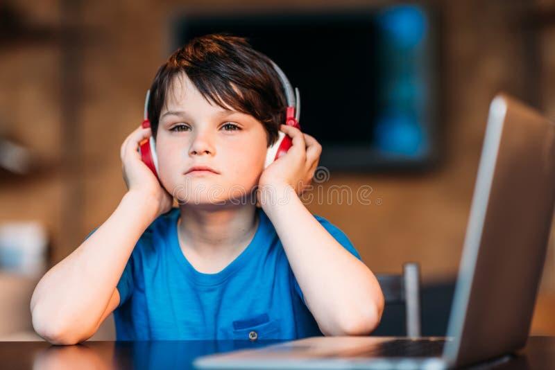 Thoughtful little boy listening music in headphones stock photo
