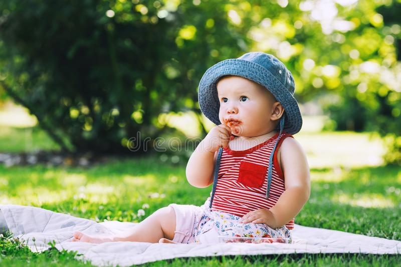 Baby eating strawberries on green nature background. Thoughtful little girl eating fresh red strawberries at first time. Baby outdoors at summertime on green stock photos