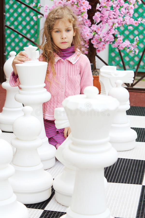 Thoughtful little girl in pink sits among large chess pieces. Thoughtful little girl in pink sits among large white chess pieces in park royalty free stock photos