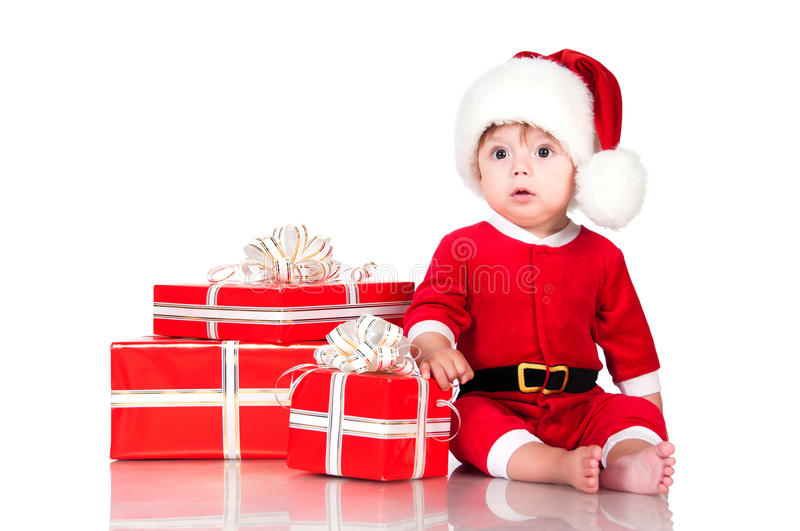 Thoughtful little Santa Claus with presents. Isolated on white b royalty free stock photography