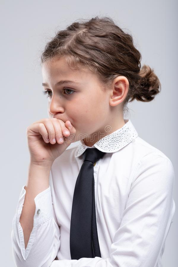 Thoughtful little schoolgirl with hand to mouth stock image
