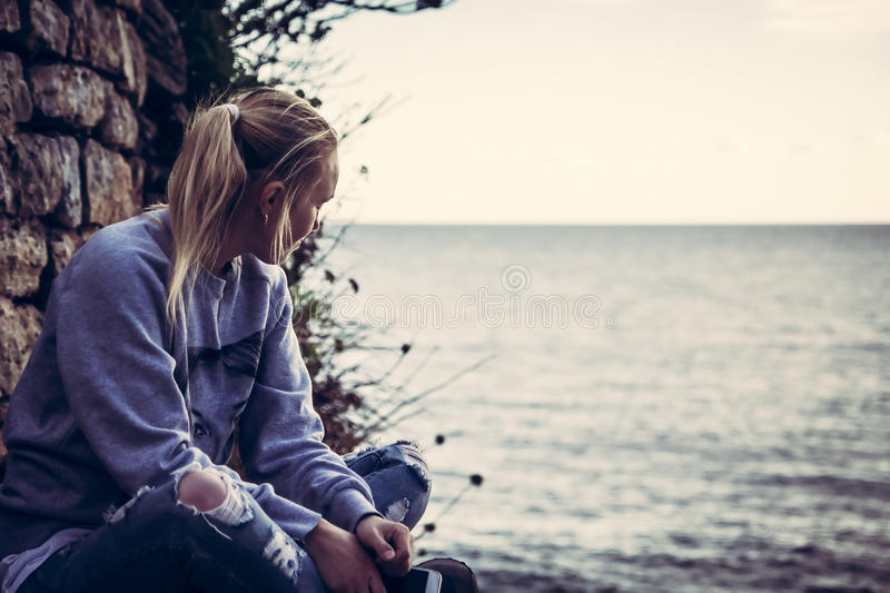 Thoughtful lonely young woman tourist with closed eyes thinking during her travel sitting on seashore in retro vintage style stock photo