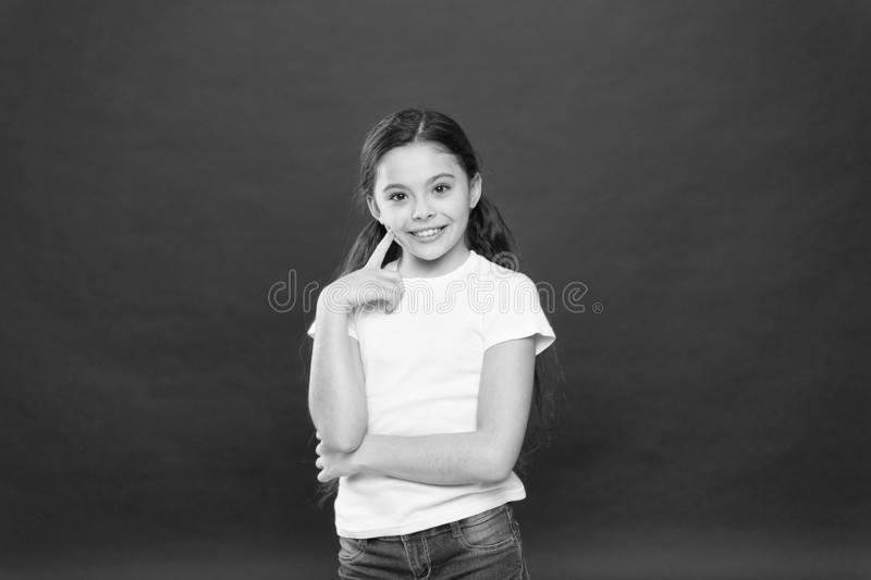 Thoughtful look of skincare model. Small girl keeping finger on cheek skin. Adorable little girl with no makeup. Beauty. Cosmetics for kids. The perfect face royalty free stock photos