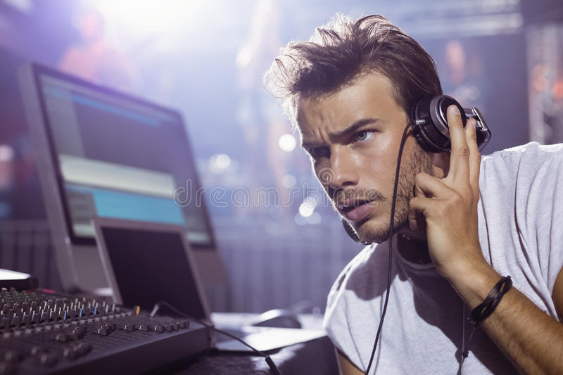 Thoughtful male dj with headphones at nightclub. During music festival royalty free stock photos