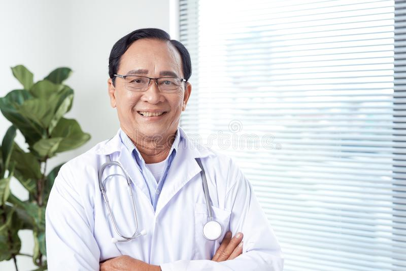 Thoughtful male doctor standing arms crossed in hospital stock photos