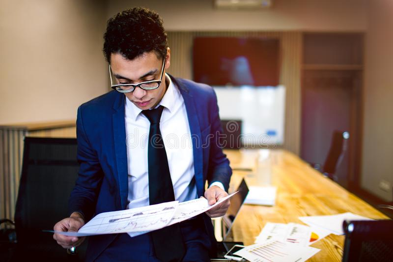 Thoughtful male entrepreneur reading paper documents stock photo