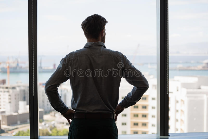 Thoughtful male executive looking through window in office stock photos