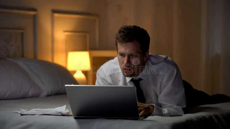 Thoughtful male lying on bed and reading documents on laptop, business e-mail royalty free stock photo