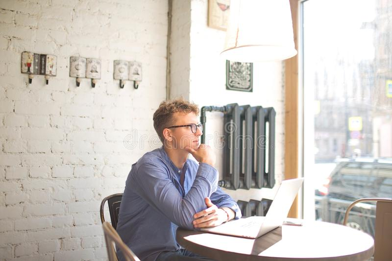 Thoughtful male marketing coordinator watching in cafe window during work on net-book royalty free stock photography