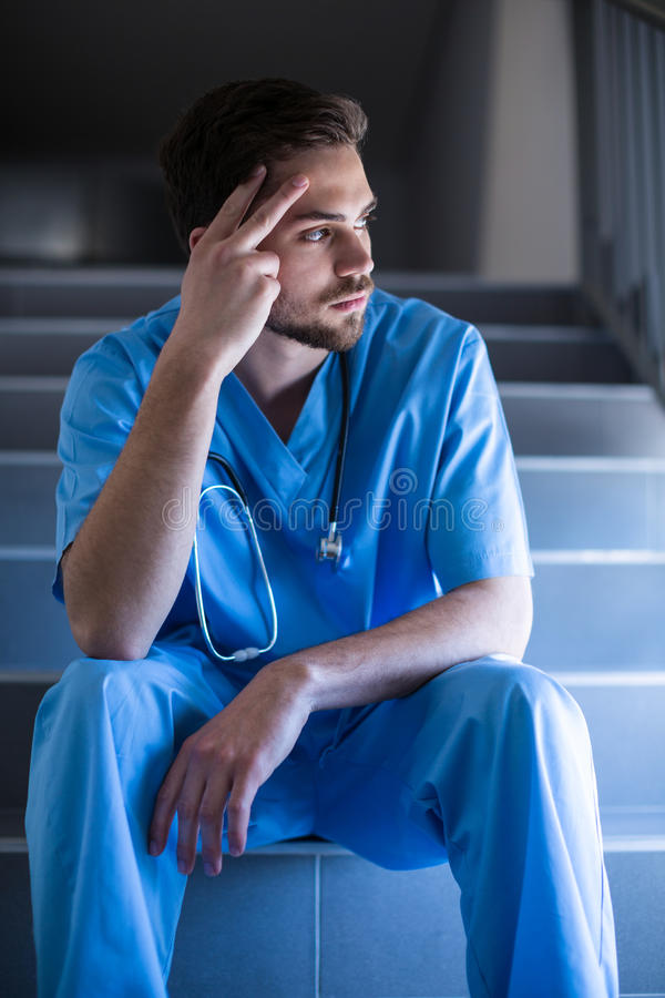 Thoughtful male nurse sitting on staircase. Of hospital stock photo