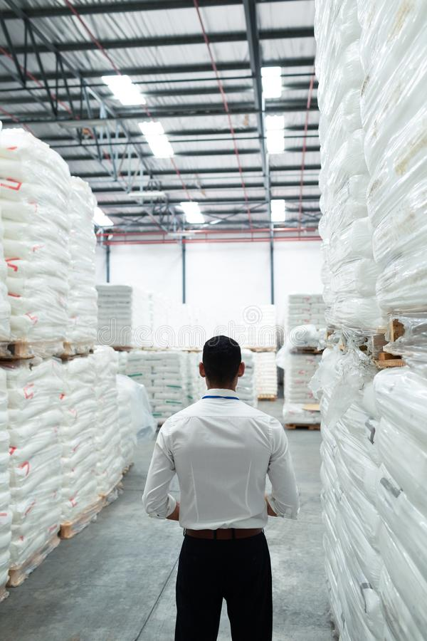 Thoughtful male supervisor standing in warehouse. Rear view of thoughtful Caucasian male supervisor standing in warehouse. This is a freight transportation and stock photo