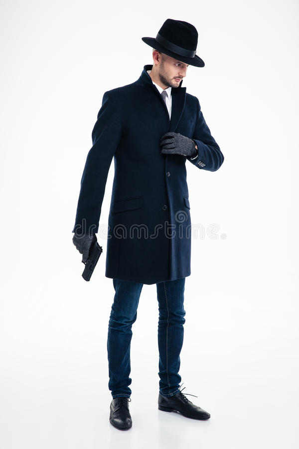 Thoughtful man in black coat, hat and gloves holding gun royalty free stock photo