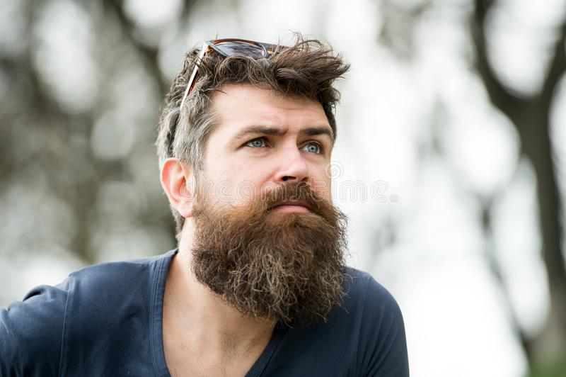 Thoughtful man with blue eyes looking into the sky, tranquility and mindfulness concept. Young bearded hipster with. Sunglasses on his head strolling in the stock image