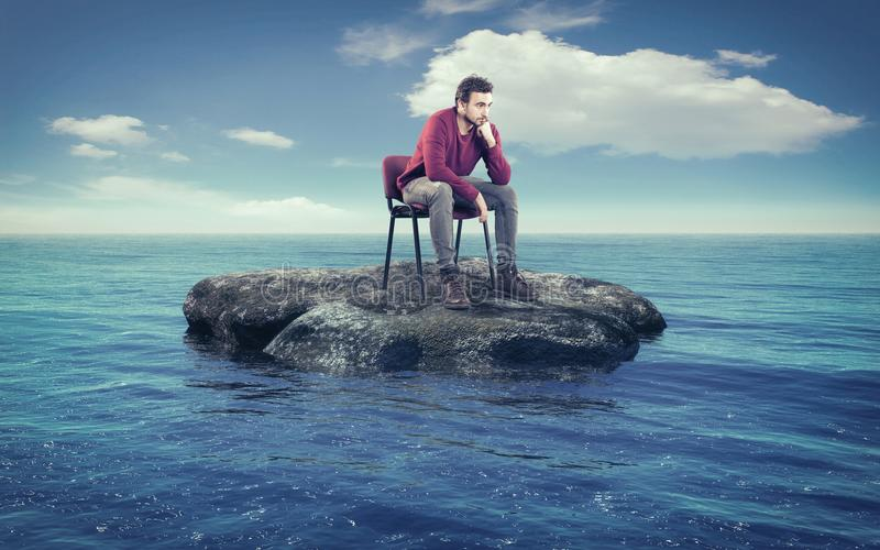 Young man thoughtfully on a chair. Thoughtful man on a chair in the middle of the ocean royalty free stock photo