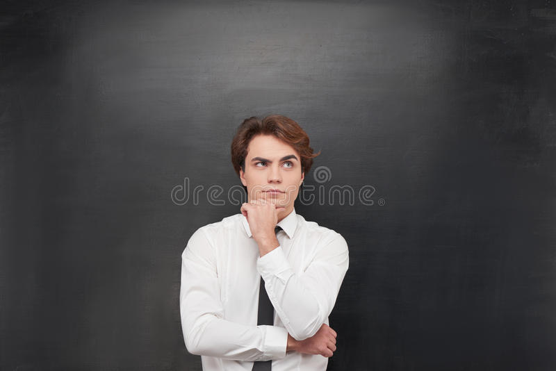 Thoughtful man on chalkboard background royalty free stock photo