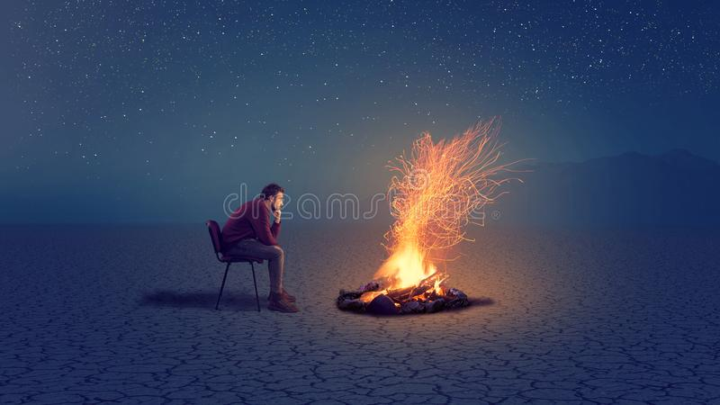A thoughtful man in front. Of a campfire into the night royalty free stock photos