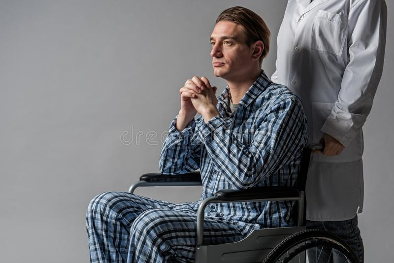 Wistful cripple cared by doctor royalty free stock photos