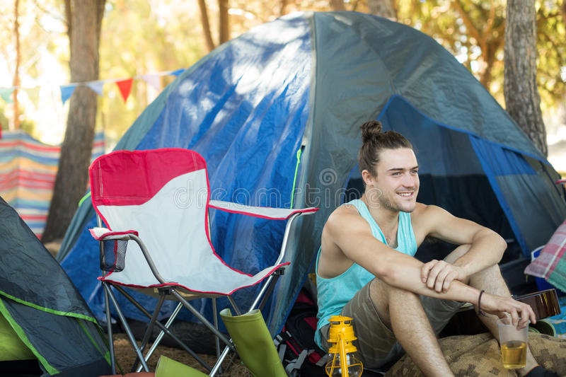 Thoughtful man holding beer glass while sitting at campsite. Thoughtful young man holding beer glass while sitting by tent at campsite royalty free stock images