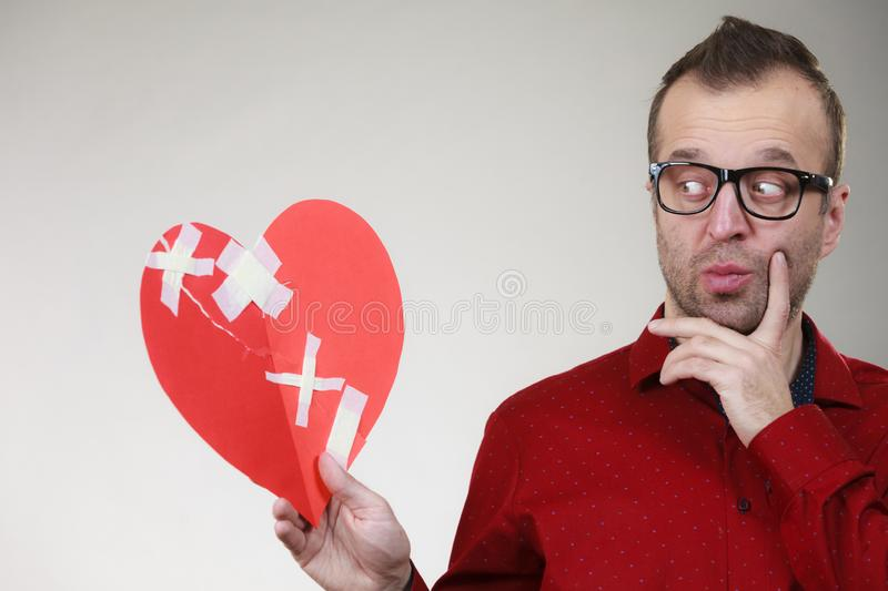 Thoughtful man holds broken heart stock image