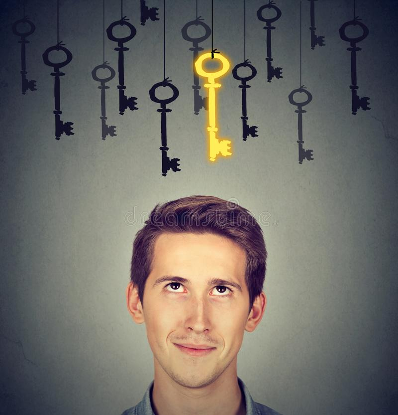 Thoughtful man looking up at vintage golden key to success among many others hanging. Concept of business aspirations, achievement stock photography