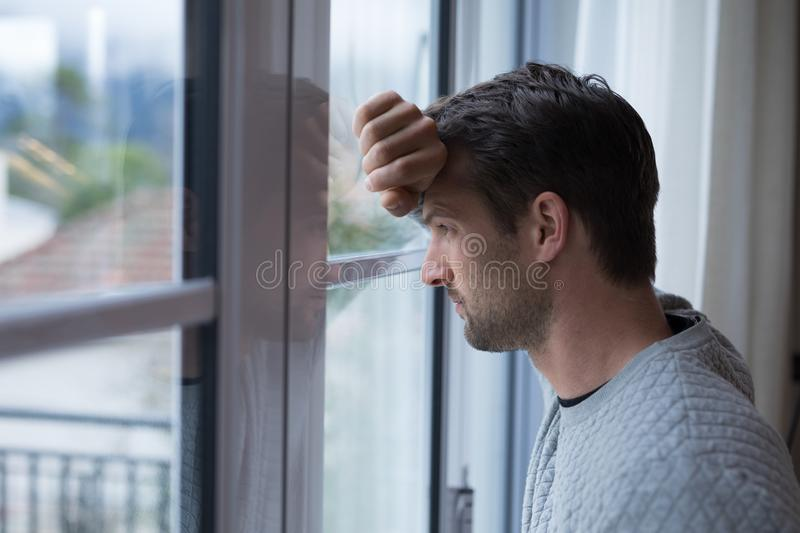 Thoughtful man looking through window stock images