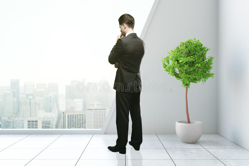 Thoughtful man in modern interior. Thoughtful businessman in modern interior with decorative plant and city view. 3D Rendering stock photos
