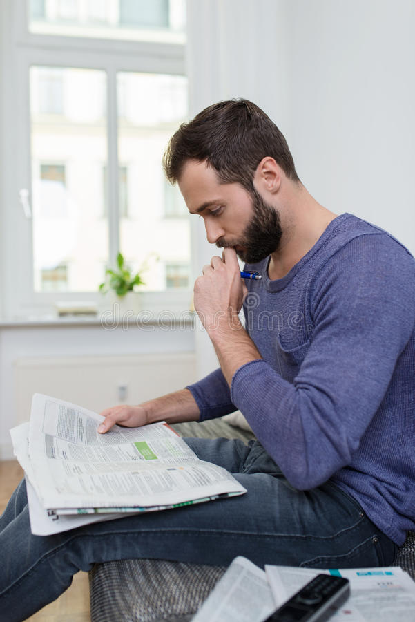 Thoughtful man sitting reading a newspaper stock image