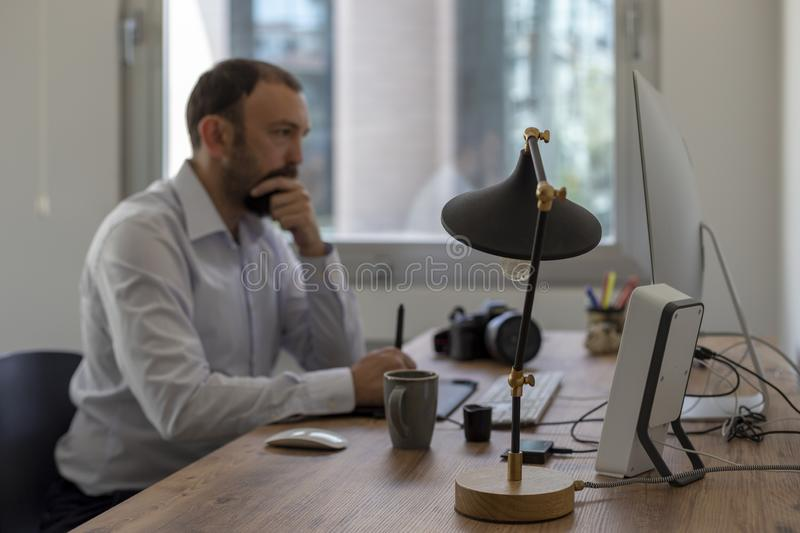 Thoughtful man sitting on a table looking to the monitor. Business man having trouble stock image