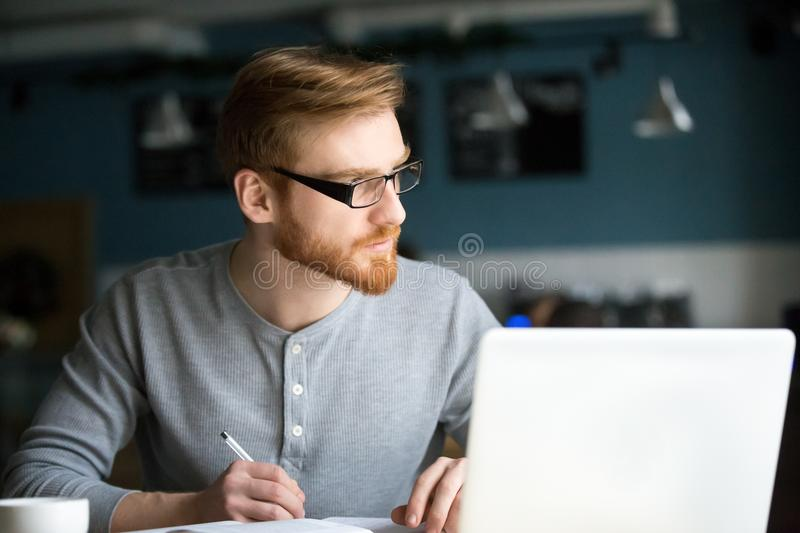 Thoughtful man thinking of new idea writing notes in cafe stock image