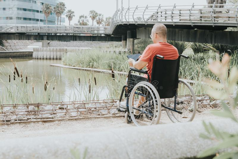 Thoughtful man in a wheelchair. Thoughtful wheelchair man looking at a lake in the city, assist, assisting, detailed, helping, operation, surgery, rehab royalty free stock image