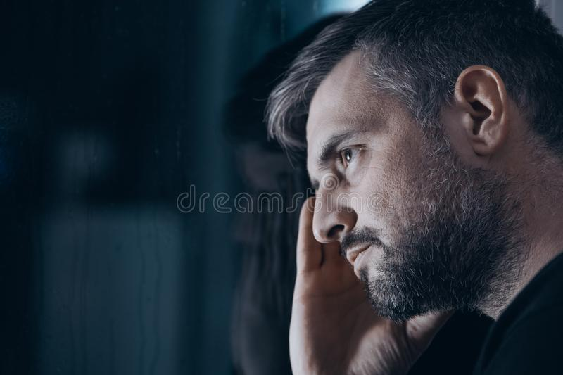 Thoughtful man with withdrawal symptoms. Close-up of thoughtful man with withdrawal symptoms looking through a window royalty free stock images
