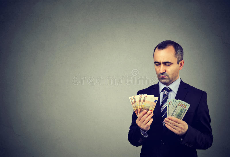 Thoughtful business man looking at euro and dollar cash banknotes. Thoughtful mature business man looking at euro and dollar cash banknotes royalty free stock image