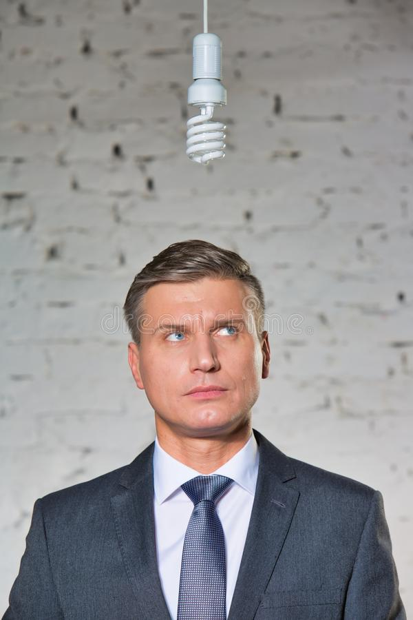 Thoughtful mature businessman looking at energy efficient lightbulb hanging against brick wall at office. Photo of Thoughtful mature businessman looking at stock photography