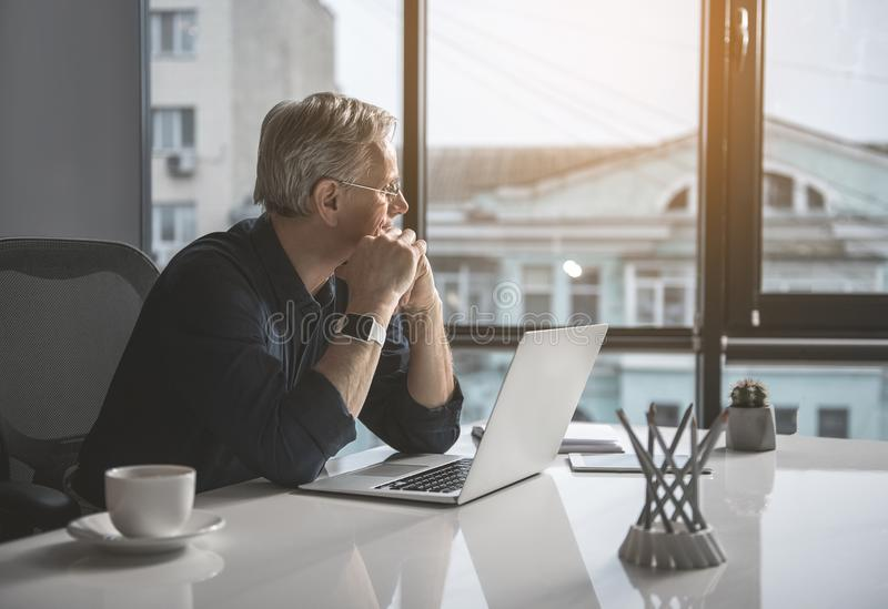 Thoughtful mature male worker watching at street stock photo