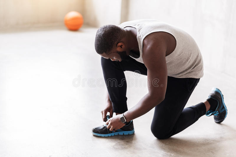 Thoughtful mature sporty man preparing for training. Pensive bearded african athlete is tying shoelaces. He is standing on bent knee. Focus on smart watch on his royalty free stock image