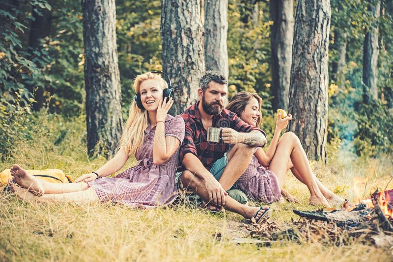 Thoughtful man with beard drinking tea of coffee while watching flames of campfire. Blond girl listening to music while royalty free stock images