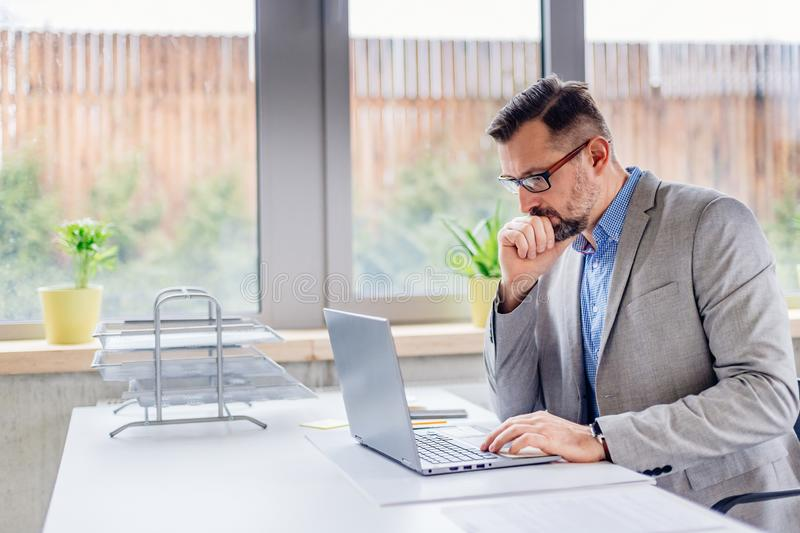 Thoughtful middle aged handsome businessman in shirt working on laptop computer in office stock photography