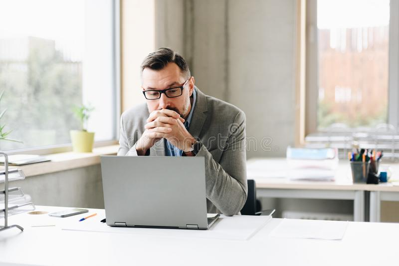 Thoughtful middle aged handsome businessman in shirt working on laptop computer in office stock image