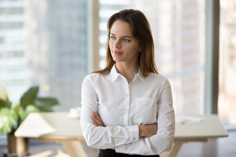 Thoughtful female employee dreaming of future success. Thoughtful millennial businesswoman looking far away, planning future goal achievement, motivated female royalty free stock photography