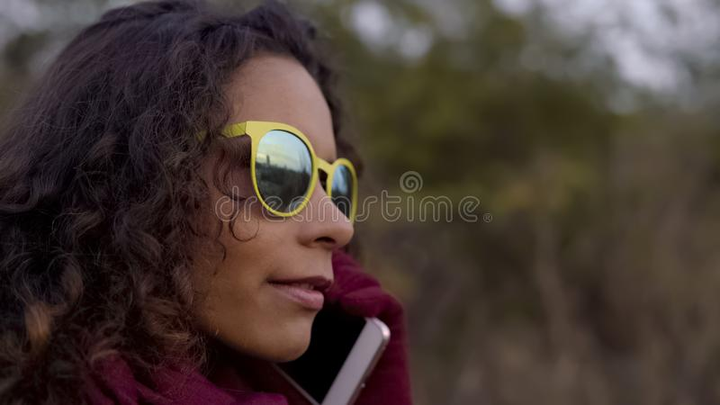Thoughtful mixed race woman in yellow sunglasses talking on smartphone, close-up royalty free stock image