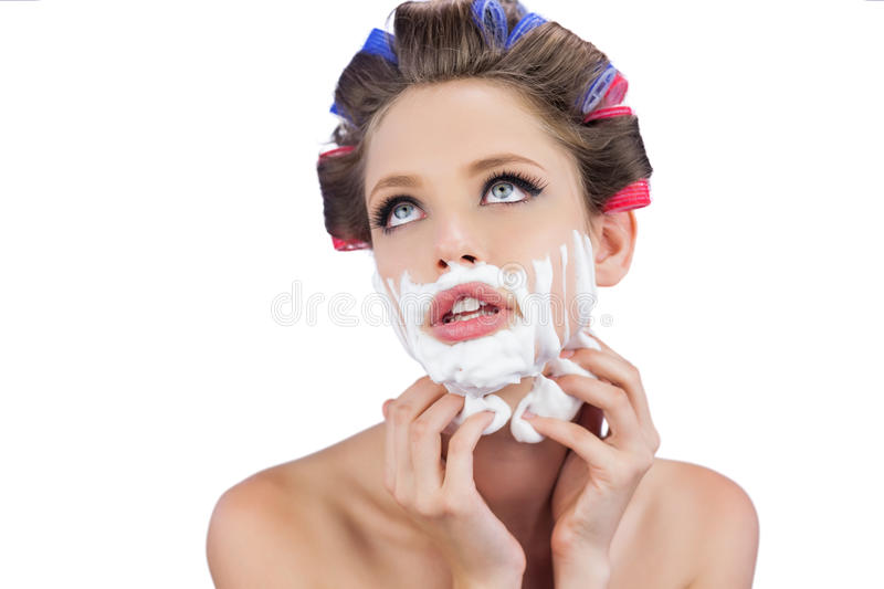 Thoughtful model touching her face with shaving foam. Thoughtful young model touching her face with shaving foam on white background royalty free stock photo