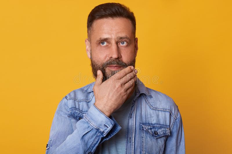 Thoughtful pensive bearded man posing with peaceful facial expression, touching his chin with one hand, looking somewhere up, royalty free stock photos