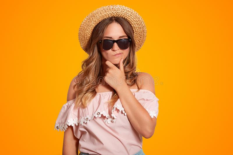 Thoughtful pensive beautiful female holds chin, has hesitant expression, wears shades and summer hat, dressed in shoulder sleeved. Blouse, poses against orange stock image