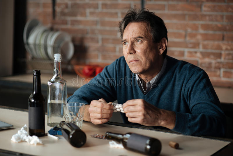 Thoughtful poor man looking upwards. Suicidal ideation. Hopeless male wrinkling forehead holding plate with pills in both hands while sitting at the table royalty free stock photography