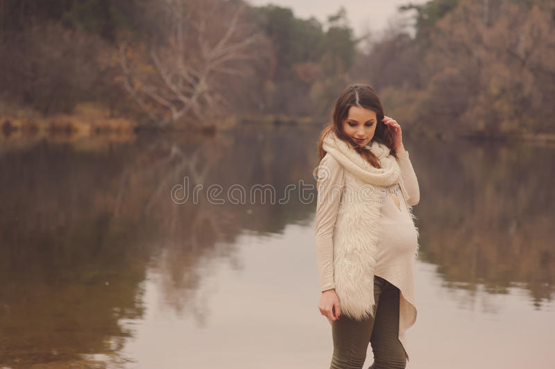 Thoughtful pregnant woman in soft warm cozy outfit walking outdoors royalty free stock images