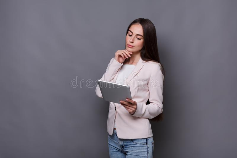 Thoughtful pretty woman with tablet stock photo
