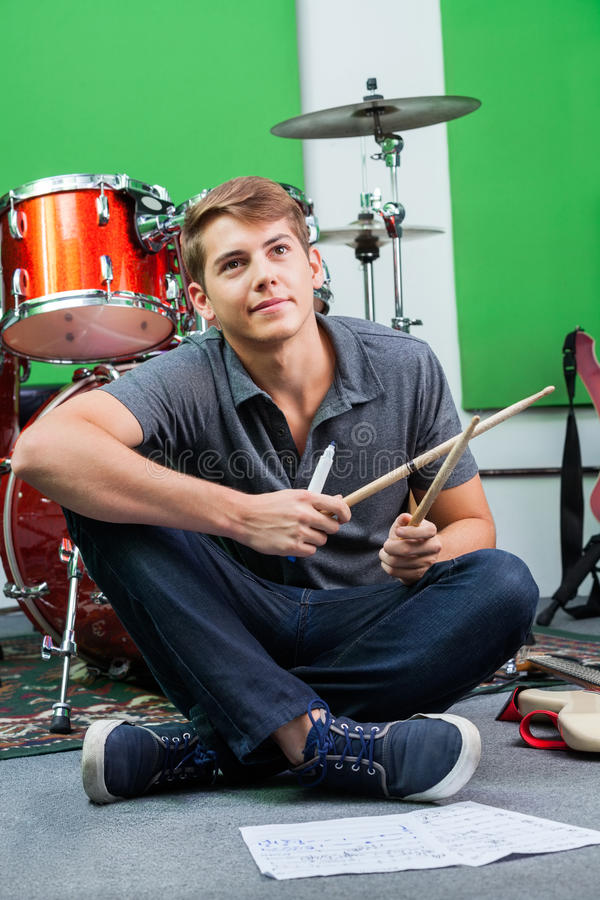 Thoughtful Professional Holding Drumsticks While Sitting On Floo stock photography