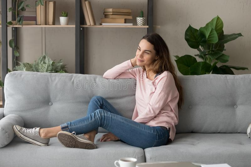 Attractive pensive woman resting on couch alone in living room royalty free stock image